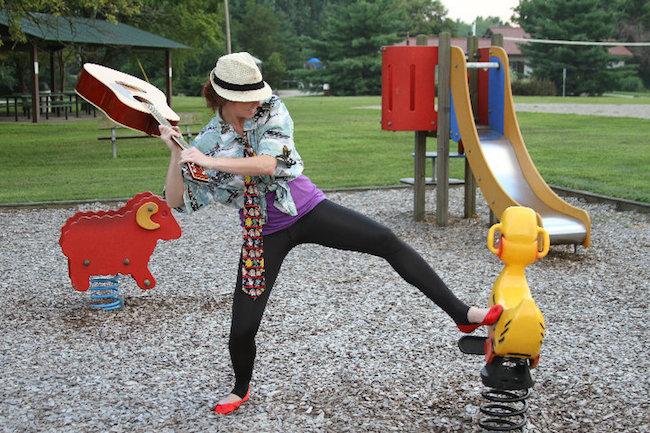 woman in crazy clothes smash guitar