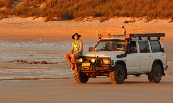 Sitting on Nissan Patrol on beach